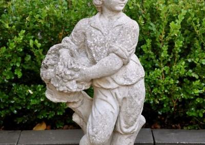 A composite stone garden figure of a boy.