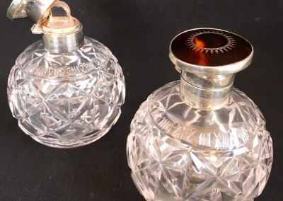 A pair of perfume bottles with sterliing silver mounts.