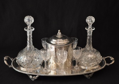 A silver plated tray with decanters, glasses and biscuit tin.