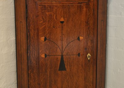 A GEO III oak corner cupboard with inlay c.1800.